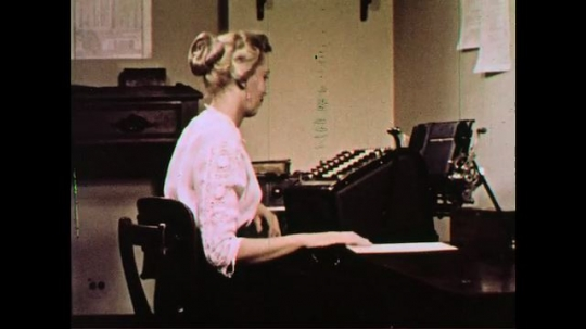UNITED STATES 1960s: A lady uses a typewriter-like machine to perform calculations.