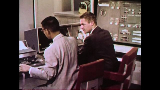 UNITED STATES 1960s: Two men sitting at a desk looking at a machine together.