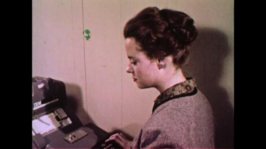 UNITED STATES 1960s: A woman encoding information into a typewriter which punches holes into a card.