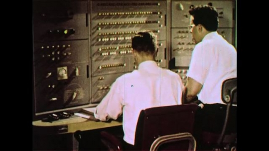 UNITED STATES 1960s: Two scientists work together to work the circuits of a computer by turning them on or off.