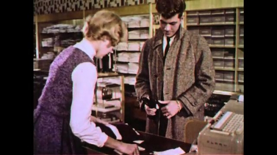 UNITED STATES 1960s: A lady rings a gentleman at a cash register.