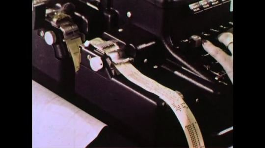 UNITED STATES 1960s: Information is punched into a roll of paper at a register.