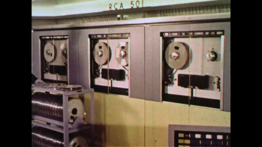 UNITED STATES 1960s: Rolls of magnetic tape containing inventory information is placed on a reel to be read by a computer.