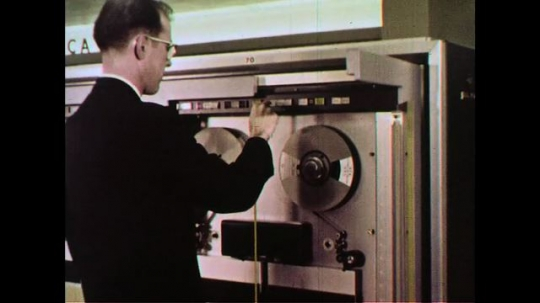 UNITED STATES 1960s: A man feeds the magnetic tape into a computer which is processed by a console operator.