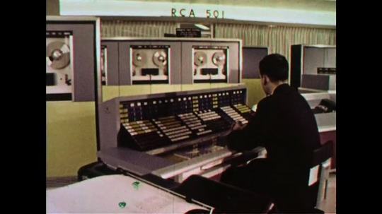 UNITED STATES 1960s: A controller works at a computer station while another one walks in.
