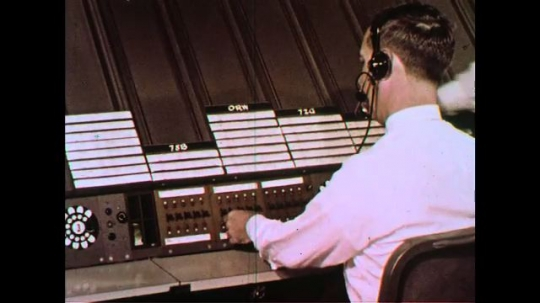 UNITED STATES 1960s: A flight control relays information to the pilot in the flying plane.
