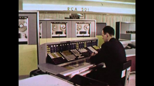 UNITED STATES 1960s: Two men work discuss some data in a control room.
