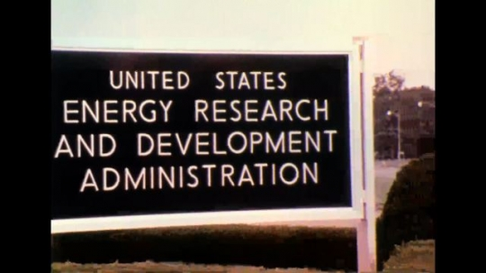 "UNITED STATES 1970s - Zoom out shot of sign that reads, ""united states energy research and development administration"". Still photo of people wearing helmets."
