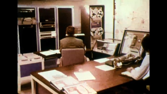 UNITED STATES 1970s - Two employees in an office environment, one at a computer.