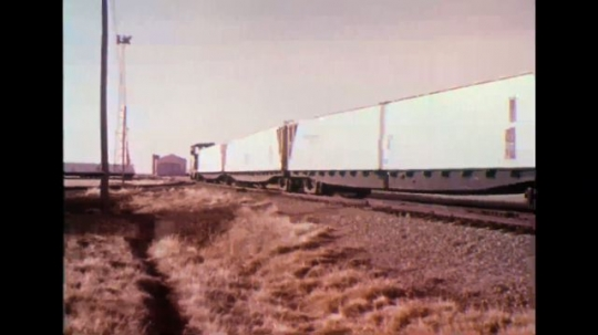 UNITED STATES 1970s - Train moving along tracks; workers outside of train.