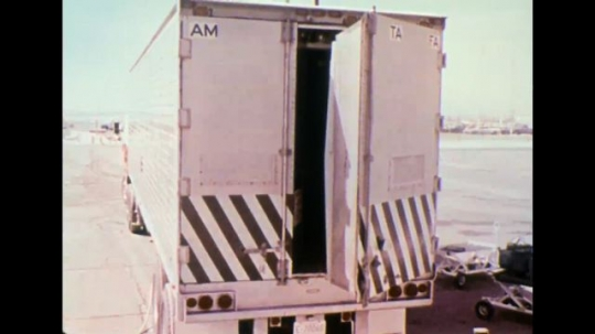 UNITED STATES 1970s - Back of cargo truck; truck and two other vehicles driving on highway.