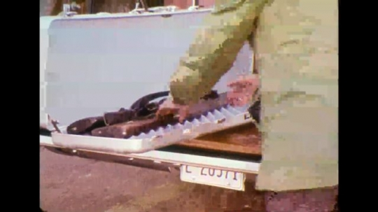 UNITED STATES 1970s - Men get rifles out of back of station wagon; man gets into station wagon with rifle.