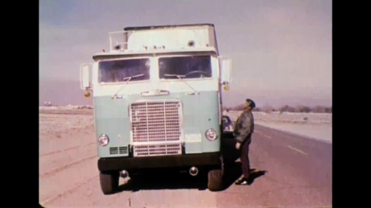 UNITED STATES 1970s - Truck driver displays photo id through window to officer and speaks into truck radio.
