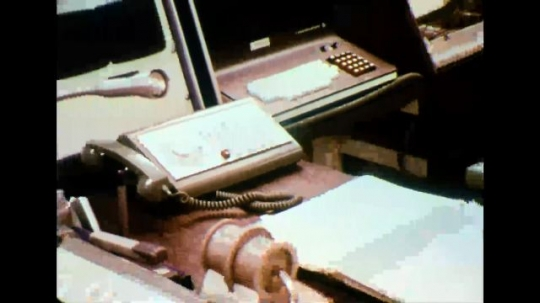 UNITED STATES 1970s - Employee answers office telephone; men exit vehicle in desert carrying rifles.