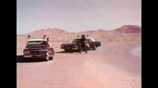UNITED STATES 1970s - Two parked police cars; man pointing gun at cars; police car driving.