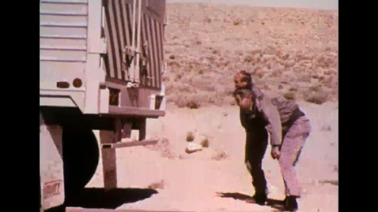 UNITED STATES 1970s - Men inspecting back of truck; man hands gun to another man in truck cab; cars in desert.