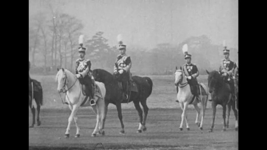 JAPAN: 1943: Emperor Hirohito rides a horse through a field followed by his entourage.