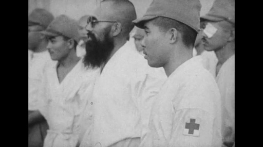 JAPAN: 1943: Japanese citizens, clothed in white robes, march together.