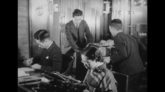 JAPAN: 1943: In a Japanese bank, gold is placed in a safe as bankers do calculations with an abacus.