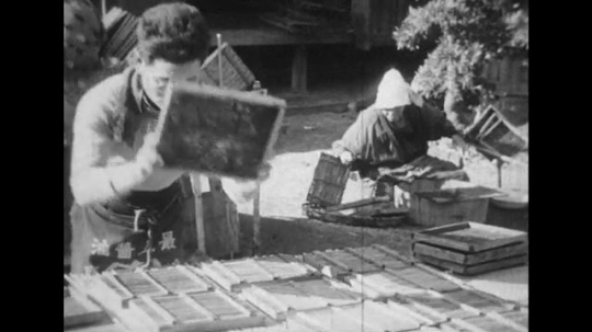 JAPAN: 1943: Women in Japanese provinces produce handicrafts as people clean the sidewalks in the villages.