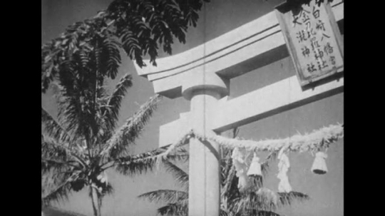 JAPAN: 1943: archway and tree branch in wind. Man Japanese dances. Man plays flute. Man plays drums. Man bangs sticks together. Close up of man