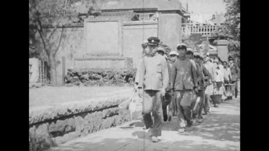 JAPAN: 1943: Men in uniform march along street with buckets. Close up of young boy in uniform. Boys take off caps.