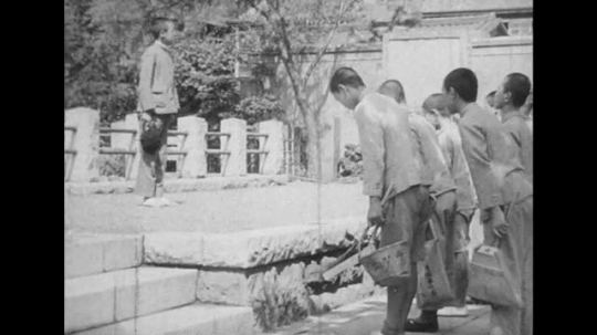 JAPAN: 1943: boys bow to boy on platform. Close up of boy's face. Boys clean.