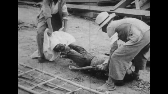 JAPAN: 1943:  People clear dead bodies from street and railway line.
