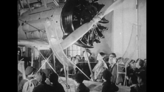 JAPAN: 1943: children and teachers visit airplane in room. Boys look up at airplane in exhibition.