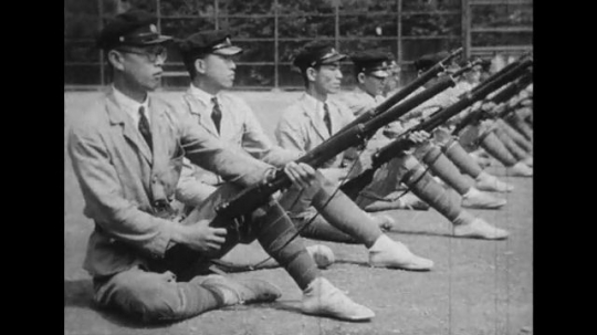 JAPAN: 1943: soldiers sit on floor and load rifles during drill practice. Close up of young man with rifle. Soldiers march through camp.