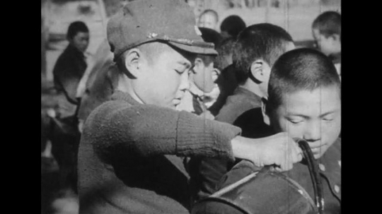 JAPAN: 1943: boy pours drink from kettle. Boys eat rice and drink tea.