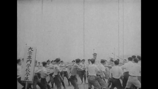JAPAN: 1943: soldiers train for battle in circle. Japanese flag in sky. Men march.