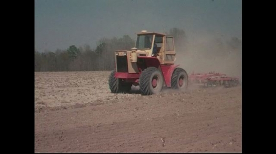 UNITED STATES CIRCA 1960s-80s : A tractor pulls equipment to till farmland.