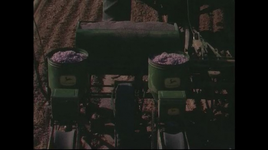 UNITED STATES CIRCA 1960s-80s : A seed planter attached to a tractor drops seeds on plowed land.