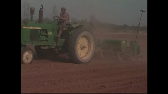 UNITED STATES CIRCA 1960s-80s : A green tractor hauls a seed planter along a few acres of farmland.