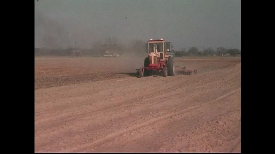 UNITED STATES CIRCA 1960s-80s : Dry soil is overturned as a tractor plows through it.