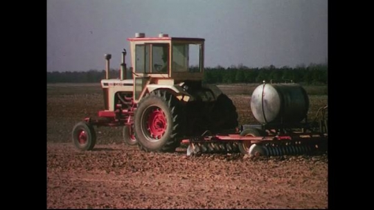 UNITED STATES CIRCA 1960s-80s : A parked tractor starts up and pulls an equipment to plow dry land.