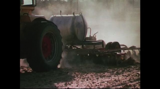 UNITED STATES CIRCA 1960s-80s : Dry soil is overturned as a farmer fills a container with water.