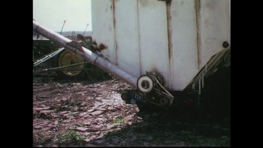 UNITED STATES CIRCA 1960s-80s : A pipe is attached to a large container as a farmer cleans his tractor.