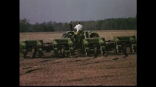 UNITED STATES CIRCA 1960s-80s : A farmer drives a tractor which is pulling equipment to water land.