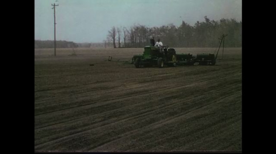 UNITED STATES CIRCA 1960s-80s : Soil is watered by a tractor pulling containers.