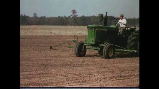 UNITED STATES CIRCA 1960s-80s : A farmer drives a tractor to water plowed land.