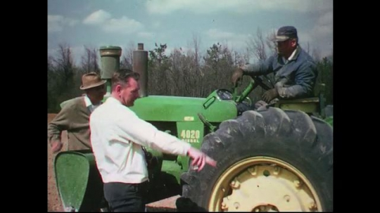 UNITED STATES CIRCA 1960s-80s : Three men talk as one man sits on a green tractor in a farm.
