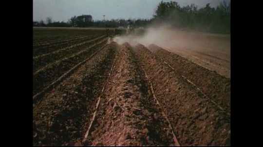 UNITED STATES CIRCA 1960s-80s : Grooves form in the soil as a tractor plows it.