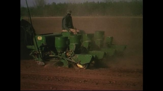 UNITED STATES CIRCA 1960s-80s : A green tractor pulls a seed planter where a man sits to inspect the droppings.