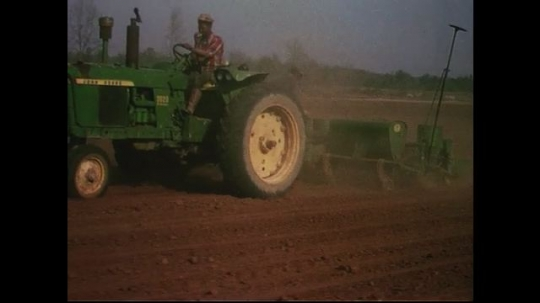 UNITED STATES CIRCA 1960s-80s : A farmer drives a tractor to plow farmland.