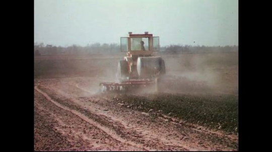 UNITED STATES CIRCA 1960s-80s : Smoke forms in the air as a tractor plows dry land.