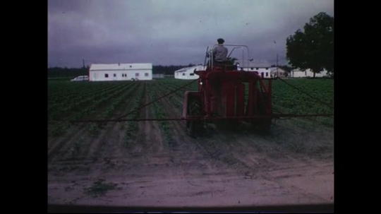 UNITED STATES CIRCA 1960s-80s : A tractor drives rapidly with a sprayer to water crops.