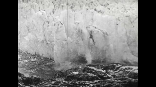 ALASKA 1960s: In the Gulf of Alaska, a piece of iceberg is submerged into the water causing a big wave to form.