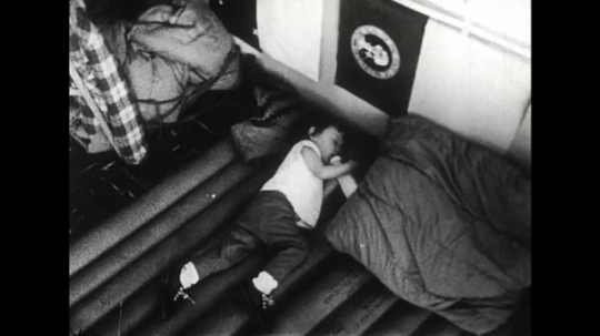 ALASKA 1960s: Temporary sleeping beds set up at a homeless shelter as trucks of army personnel drive to the scene.